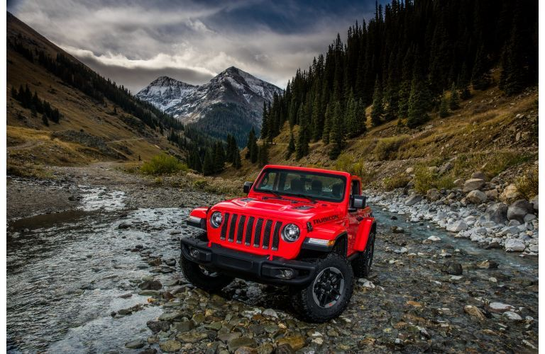 2021 Jeep Wrangler Rubicon red driving over stream facing forward