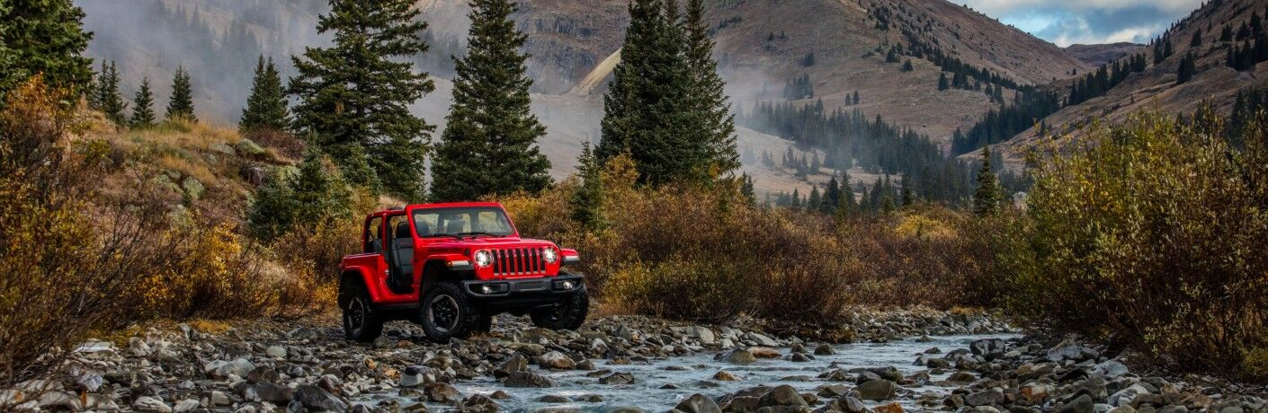2021 Jeep Wrangler Rubicon red parked by stream