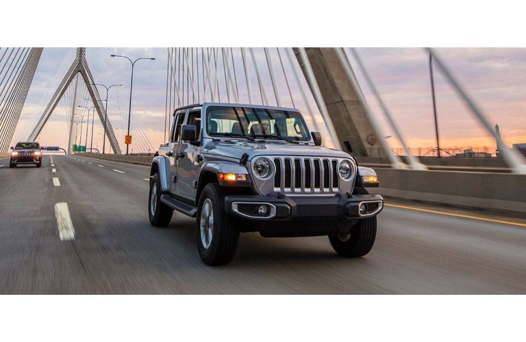2021 Jeep Wrangler gray driving over bridge under sunset clouds