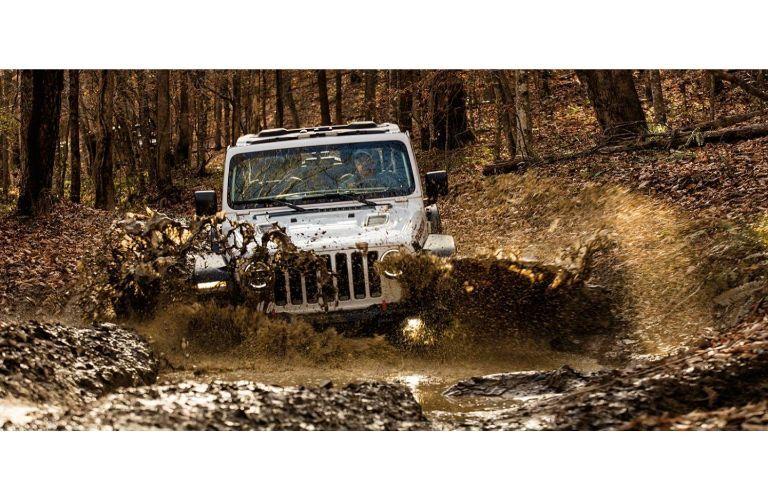 2021 Jeep Wrangler white diving into deep mud and splashing