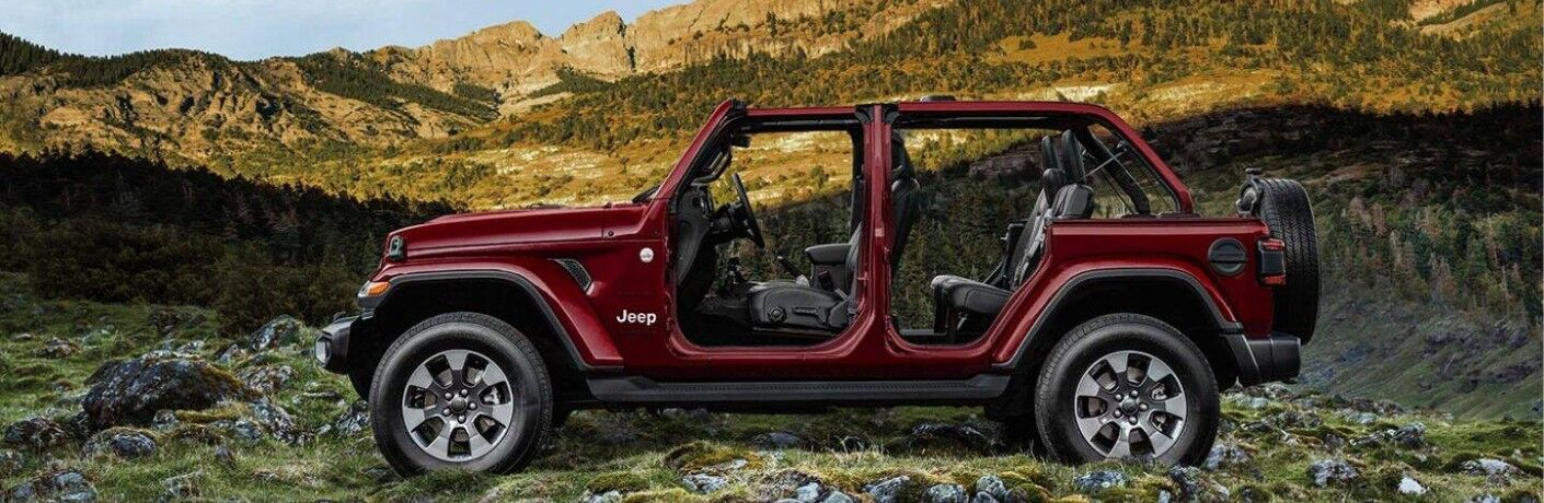 2021 Jeep Wrangler without doors red parked on rocky grass