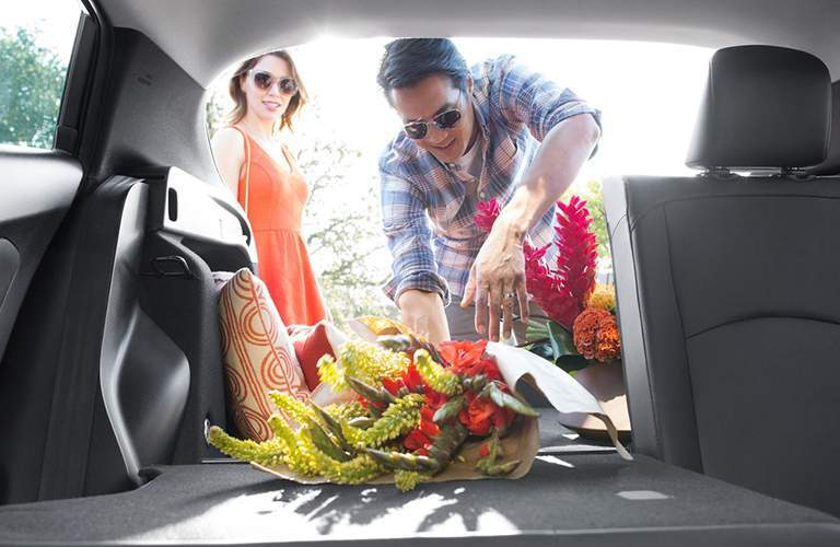 Back seats, folded down, of a 2018 Toyota Prius its loaded by man with flowers.