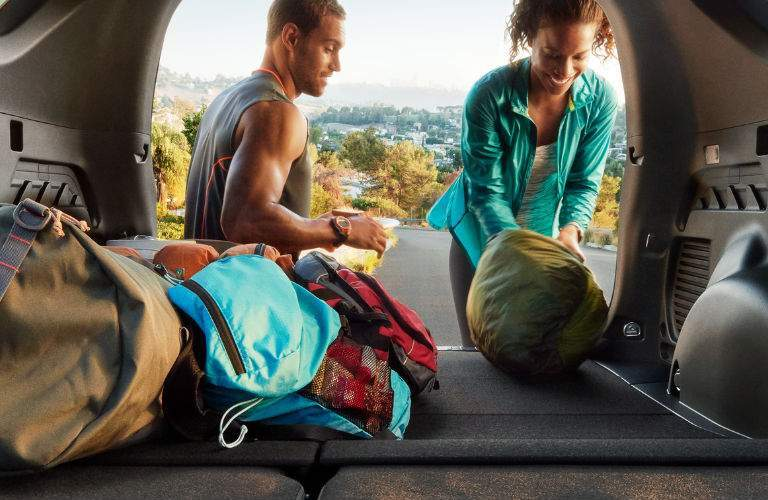 two people loading camping gear inside the cargo area of the the 2018 Toyota RAV4 with its seats folded down