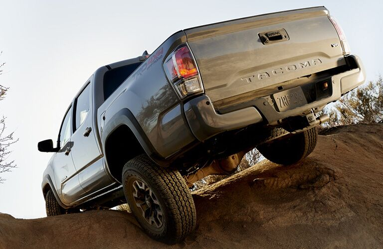 rear view of 2020 Toyota Tacoma driving over rocky terrain
