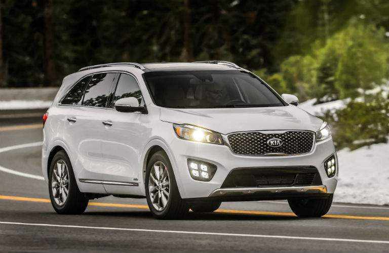 2018 Kia Sorento front passenger side profile, headlights and grille of a curvy road surrounded by snow