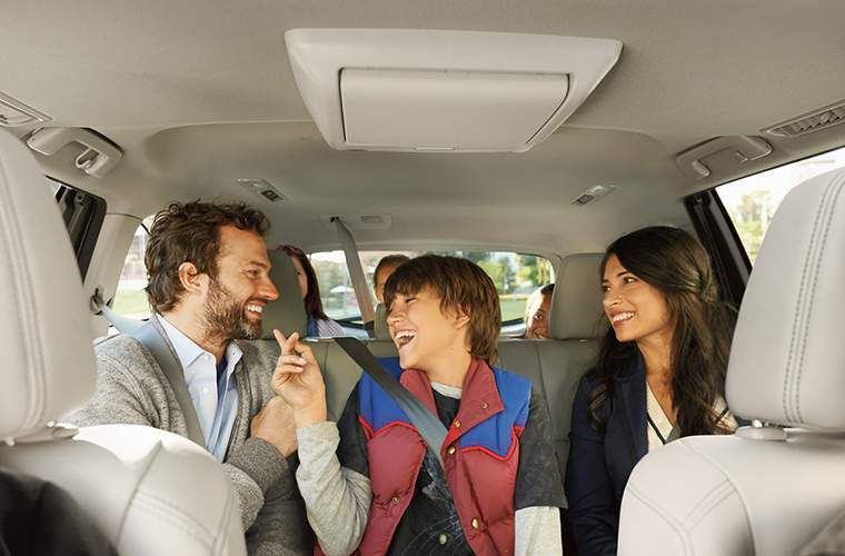 Happy family laughing at each other in back seat of 2018 Toyota Highlander