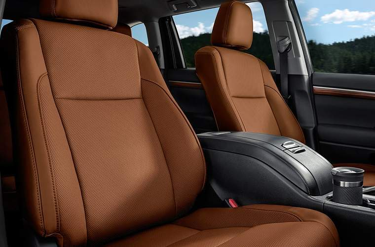Front two seats of 2018 Toyota Highlander with center console prominently displayed