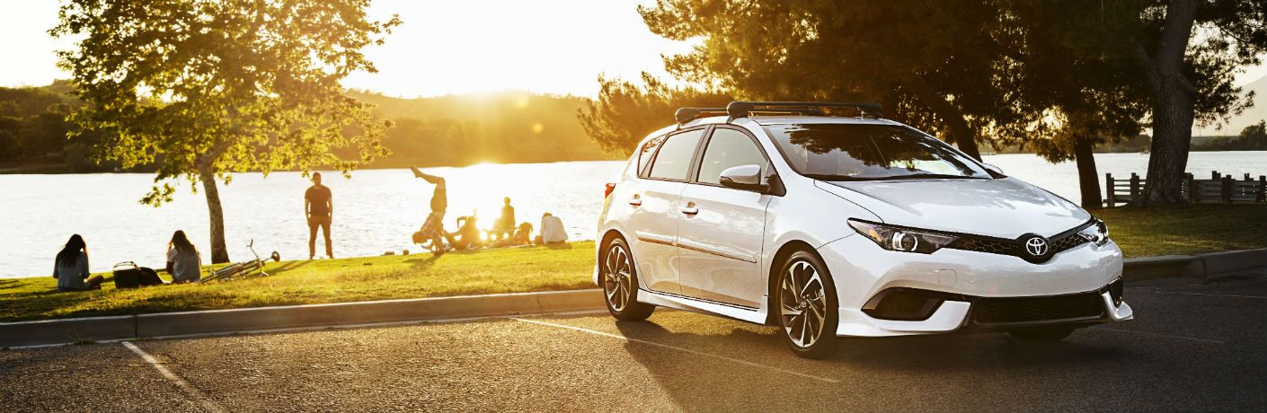 A front quarter photo of a 2018 Corolla iM parked near people having a picnic.