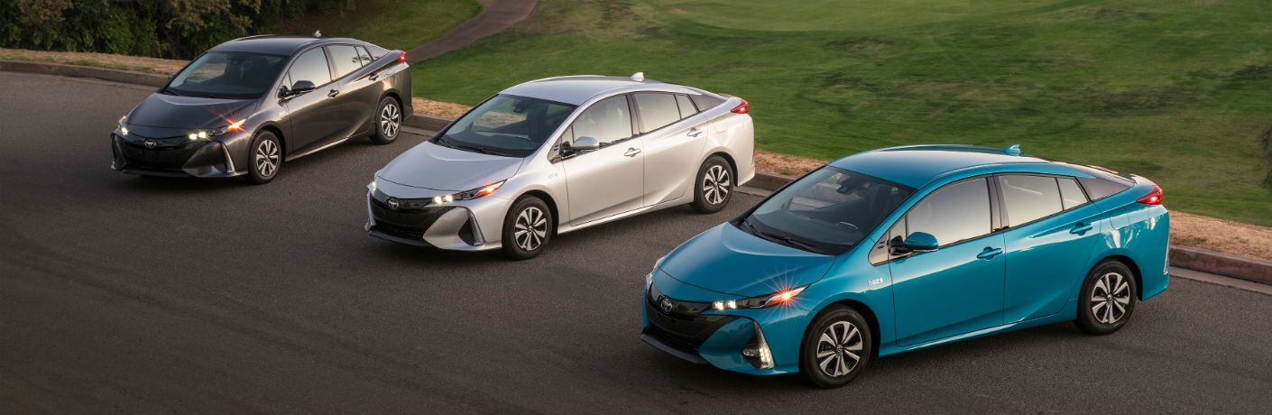 An overhead photo of three models of the 2018 Toyota Prius Prime in a parking lot.