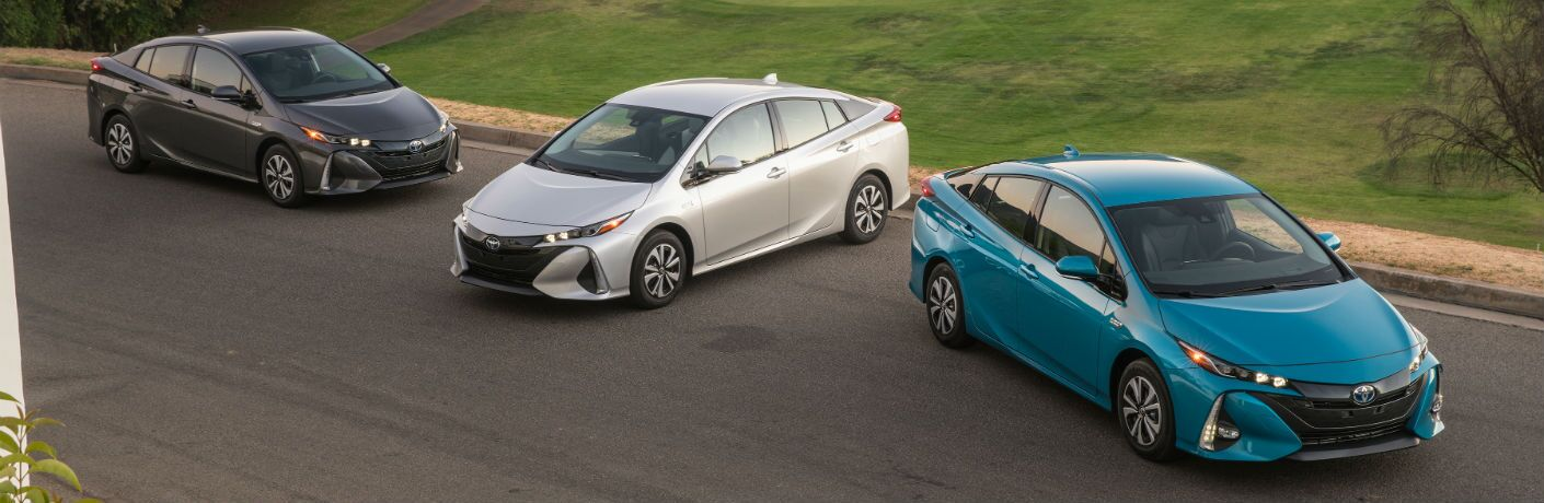 An overhead photo of all three trims of the 2018 Toyota Prius Prime lined up on the side of the road.