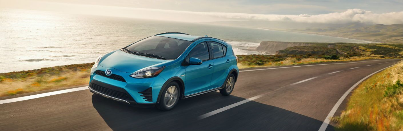 A photo of a 2018 Toyota Prius c driving on a road next to the ocean.