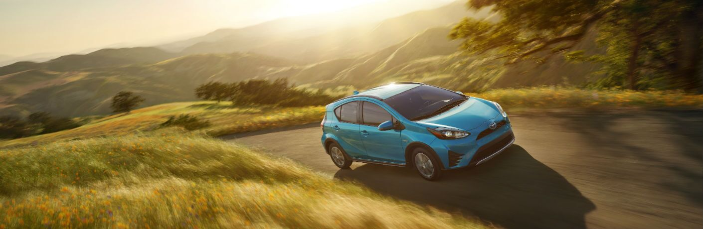 An angular overhead photo of the 2018 Toyota Prius c driving through a field.
