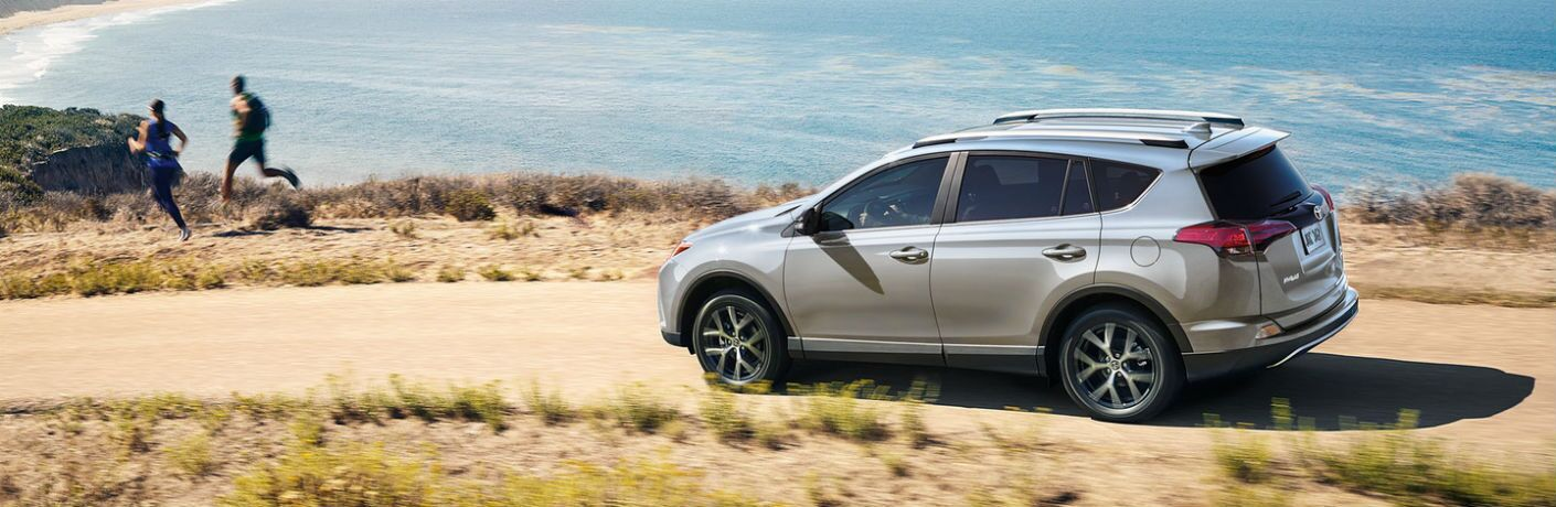 A left profile photo of a 2018 Toyota RAV4 driving on a gravel road.