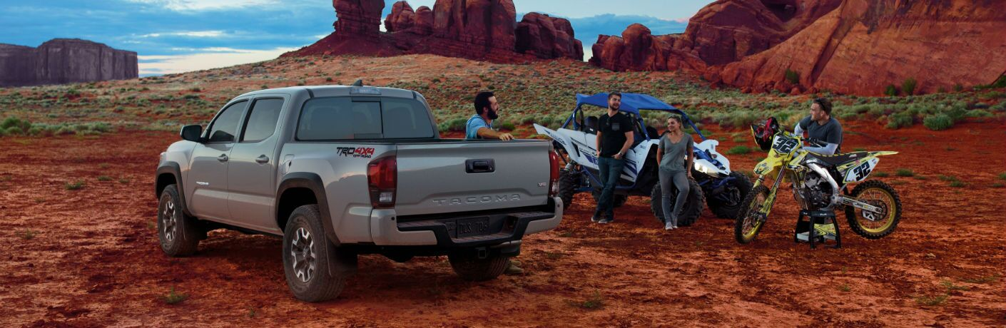 A photo of people congregating around a Toyota Tacoma.