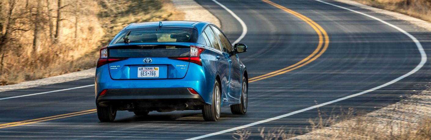 A rear photo of the 2019 Toyota Prius on the road.
