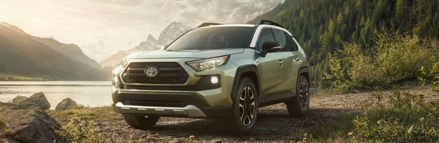 A front left quarter photo of the 2019 Toyota RAV4 parked by a lake.