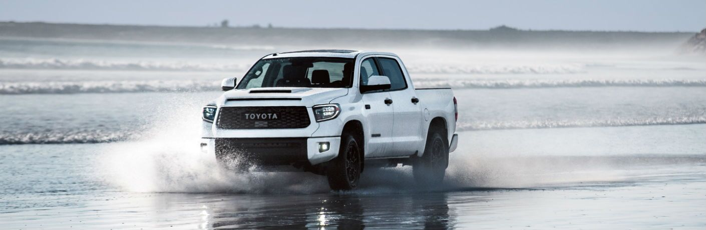 A photo of the 2019 Toyota Tundra driving on a beach by the ocean.