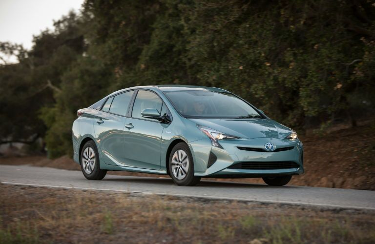 A front right quarter photo of the 2018 Toyota Prius in motion on the road.
