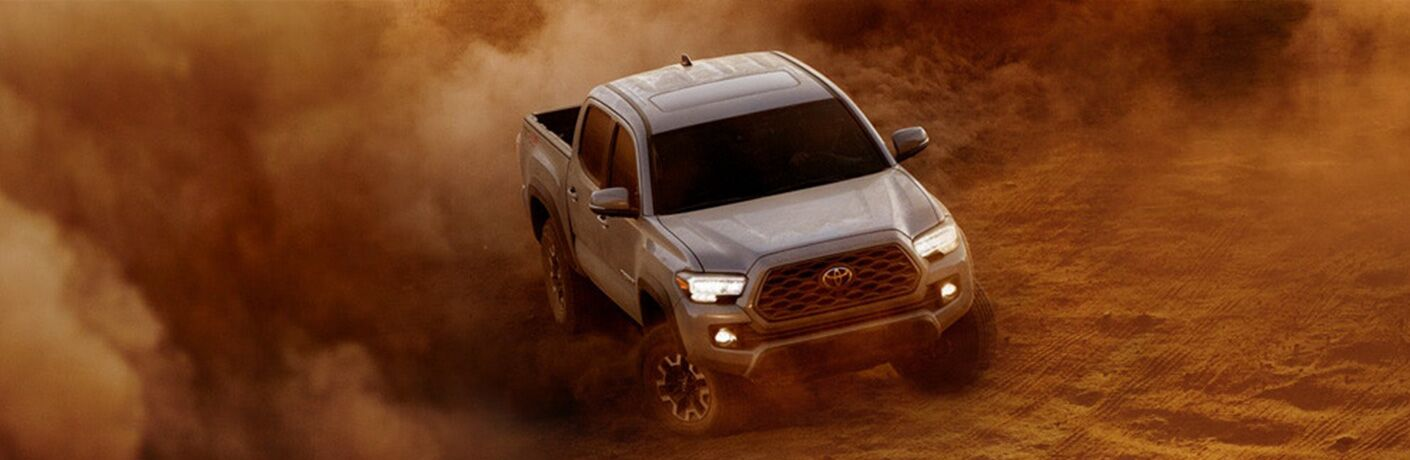 A photo of the 2020 Toyota Tacoma driving aggressively through the desert.