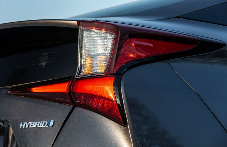 A rear right quarter photo of the 2019 Prius showing its hybrid badge.