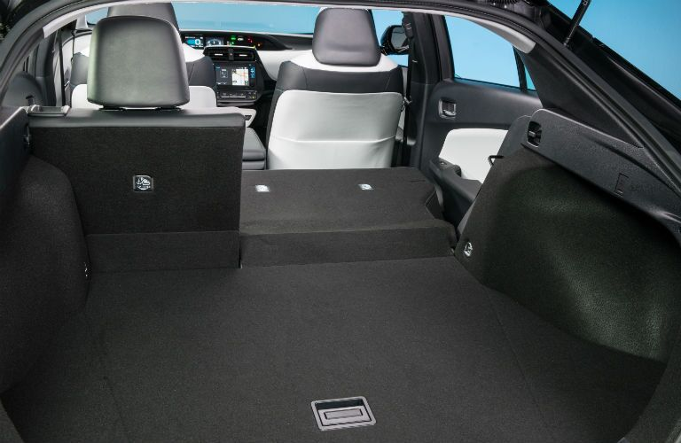 An interior photo of the rear seats partially folded down in the 2018 Prius.