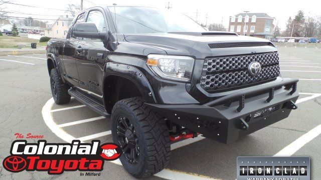 A front right quarter photo of a customized black Toyota Tundra.