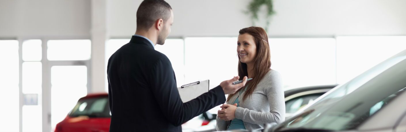 A stock photo of a dealership representative helping a customer in a showroom.