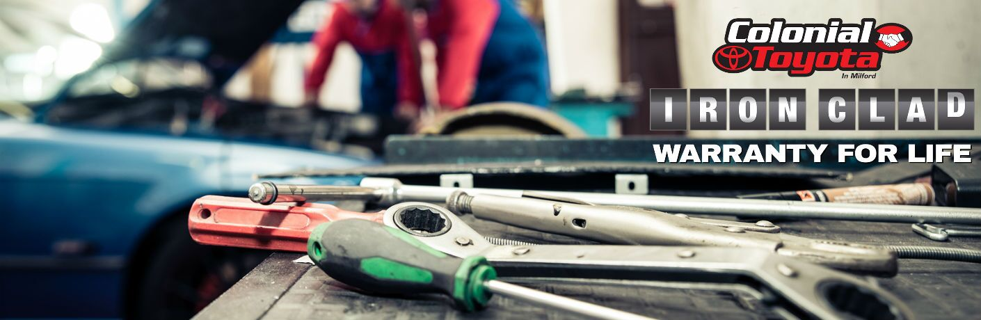 A stock photo showing tools and people working on a car with the Colonial Toyota Iron Clad Warranty for Life logo in the corner.