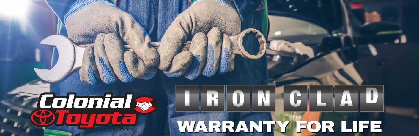A stock photo of a mechanic holding a wrench with the Colonial Toyota Iron Clad Warranty for Life logo on the photo.