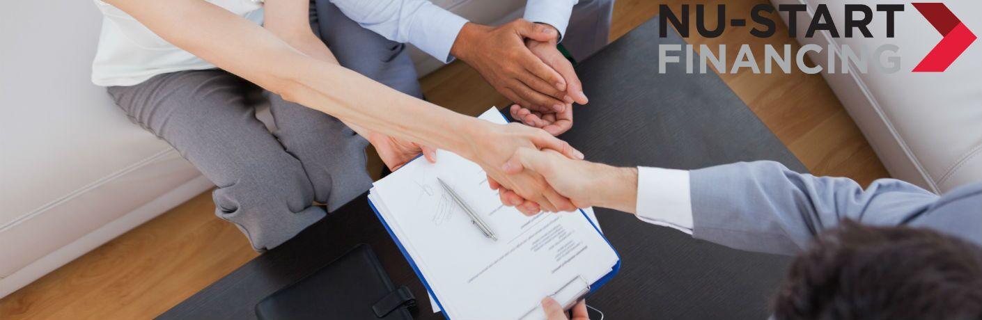 An overhead photo of people completing a deal with a hand shake with a Nu-Start Financing logo.
