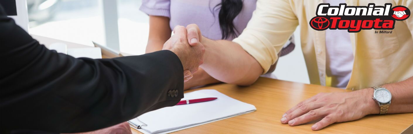 A stock photo of people shaking hands after completing paperwork with a Colonial Toyota logo on it.