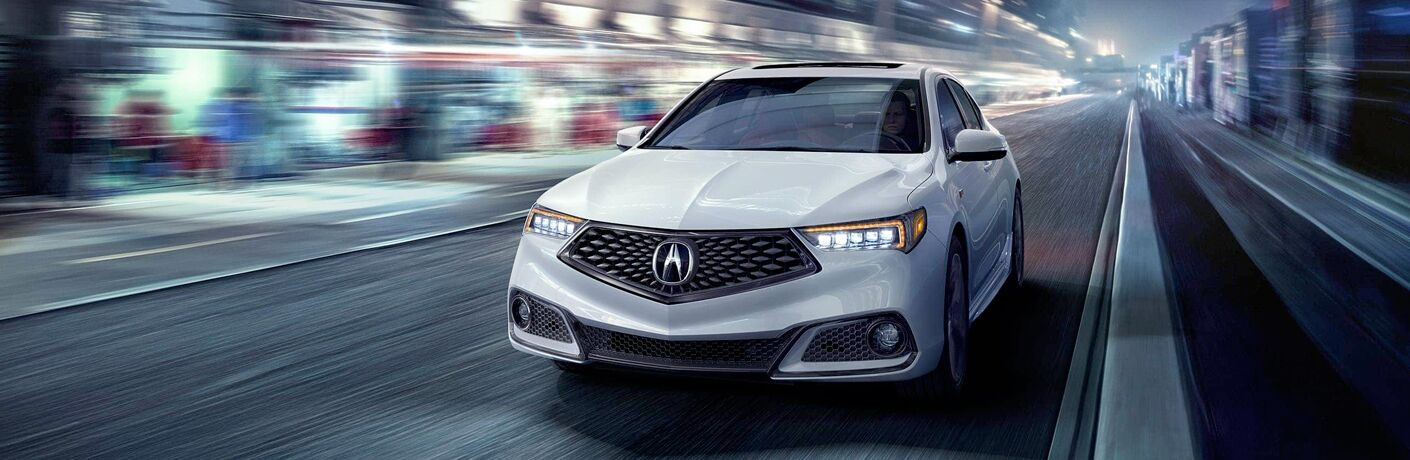 White 2018 Acura TLX driving on dark city road