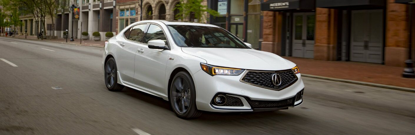 White 2019 Acura TLX driving on downtown city road