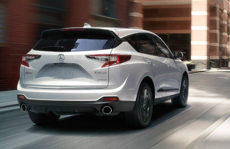 Rear shot of white 2019 Acura RDX driving on city street