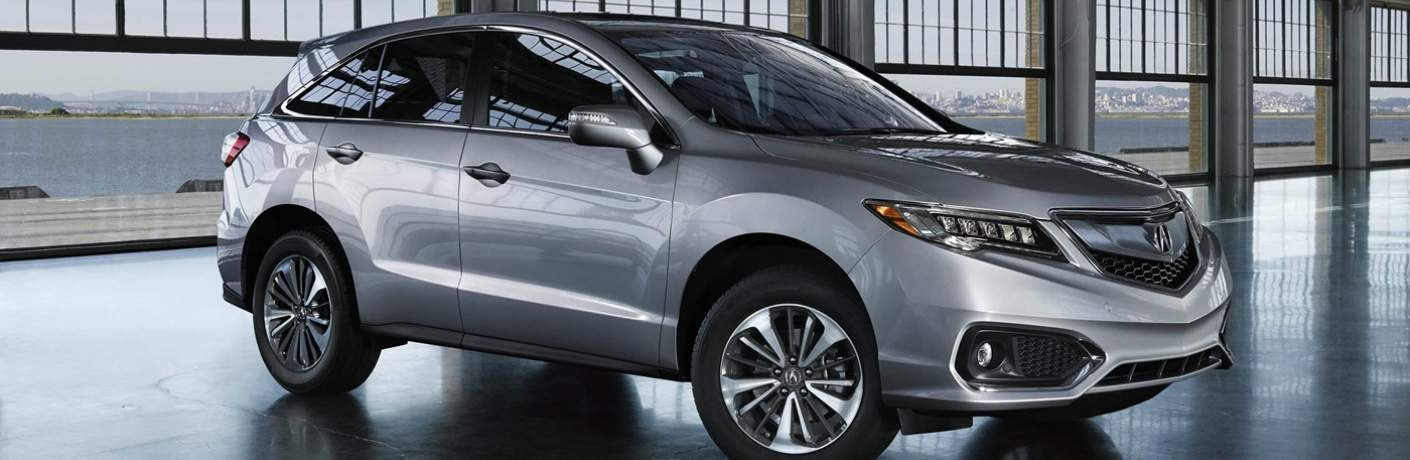 Profile view of silver Acura RDX in building