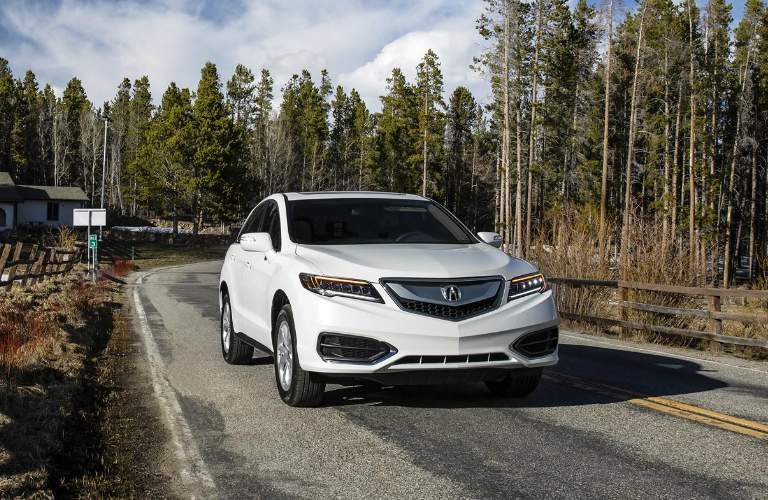 White Acura RDX driving down wooded road