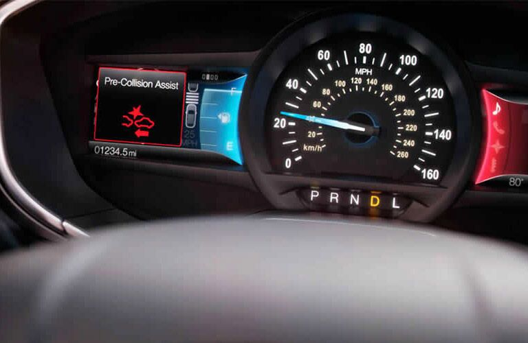 """Ford Fusion instrument cluster with digital warning message that says """"Pre-Collision Assist"""""""