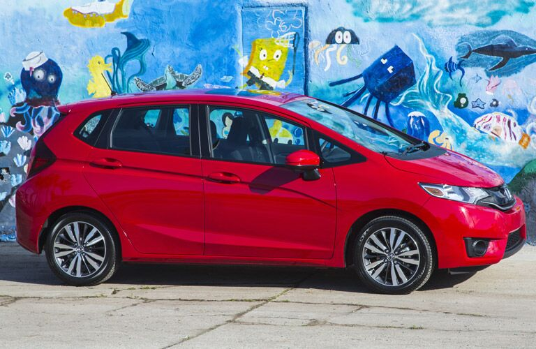 red honda fit in front of a mural