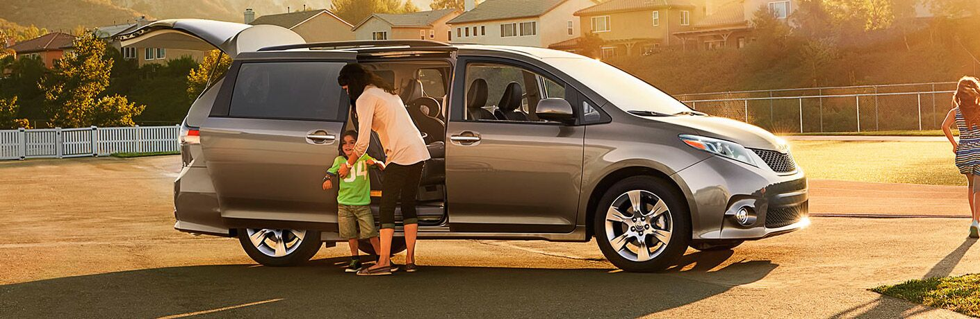 mom helping child get out of a Toyota Sienna