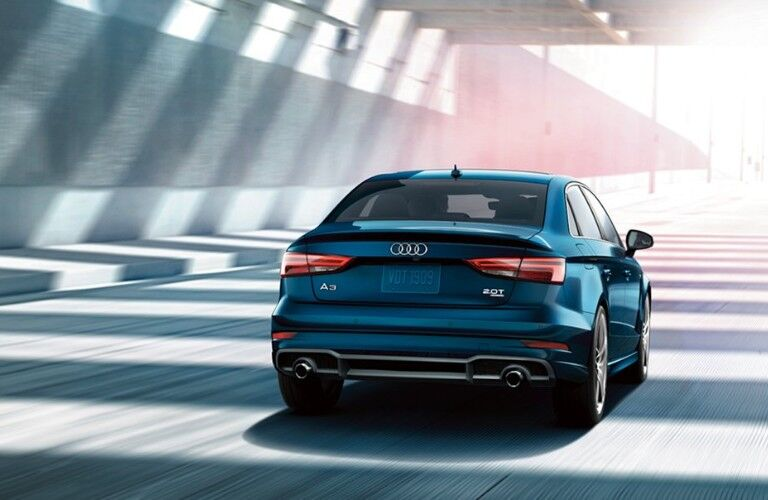 Rear passenger angle of a blue 2018 Audi A3 driving