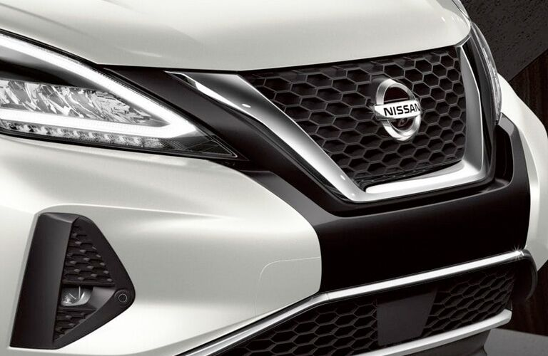 Close up of the front passenger angle of a white 2019 NIssan Murano headlight and grille