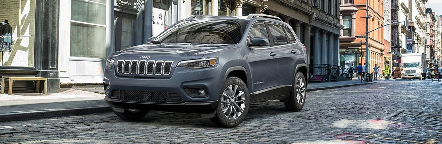 Front driver angle of a grey 2019 Jeep Cherokee parked on the side of a street