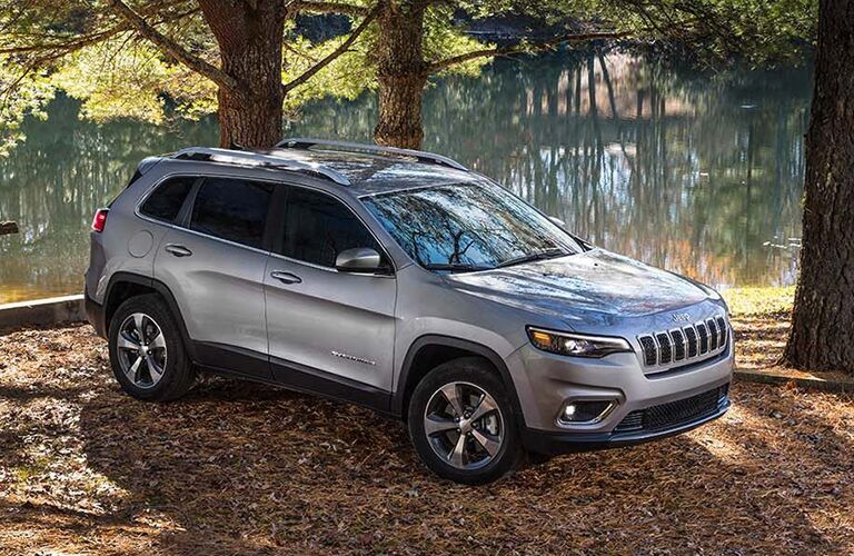 Front passenger angle of a grey 2019 Jeep Cherokee parked outdoors by a lake