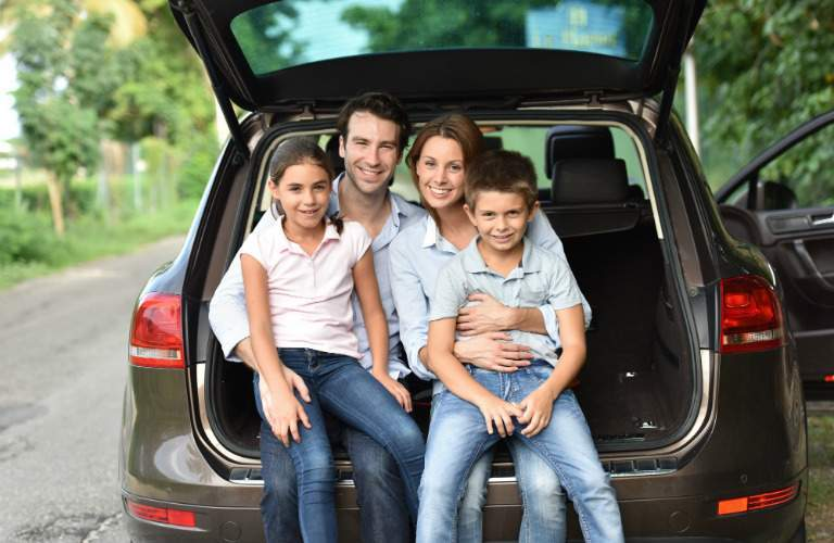 Family of four sitting on the back end of their car
