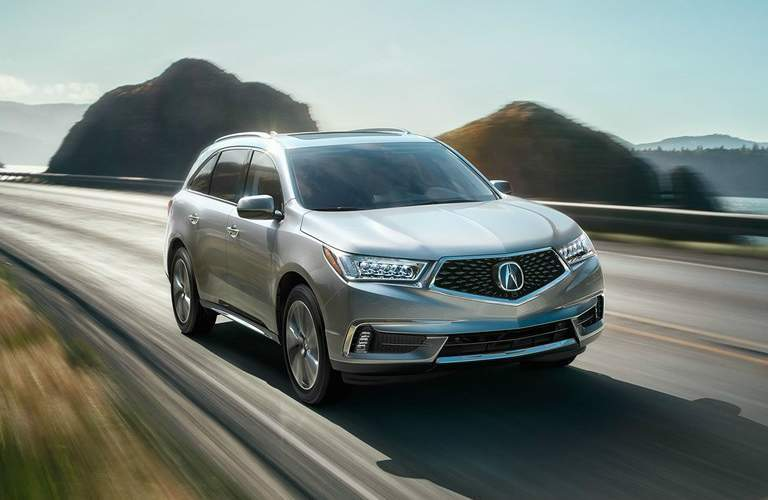2017 Acura MDX driving on open road near water body