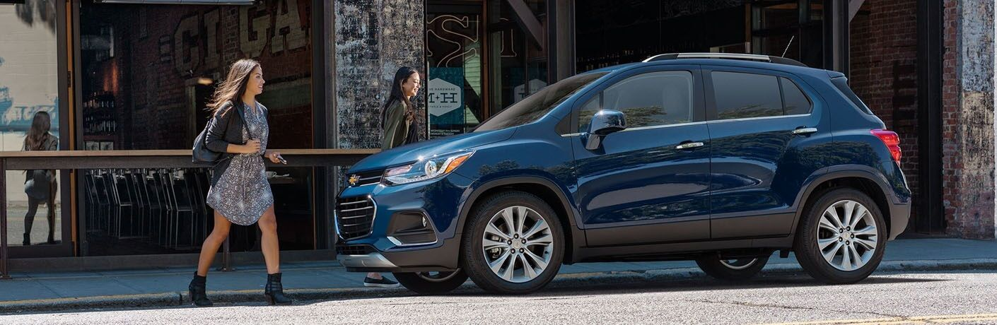 Two women walking beside a 2019 Chevy Trax