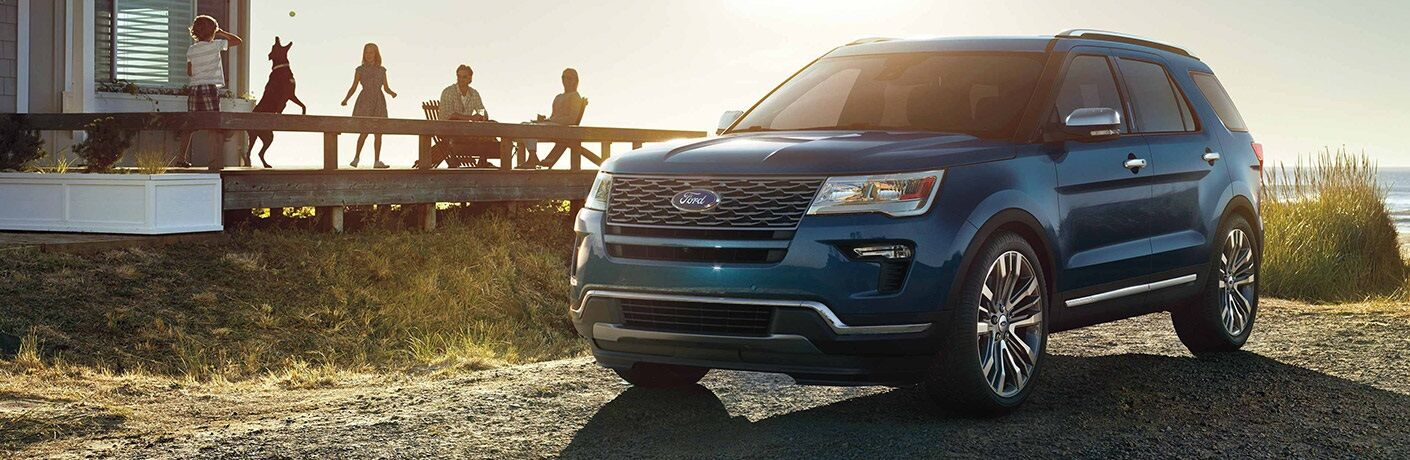 Blue 2019 Ford Explorer parked outside home with family outside