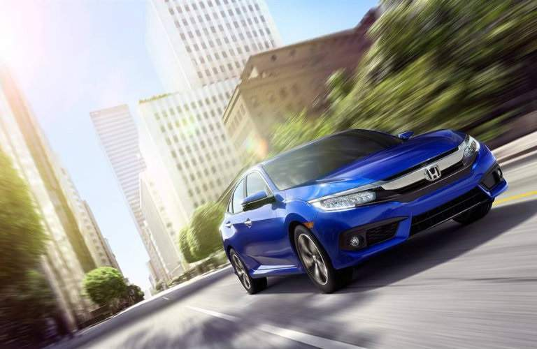 Blue 2016 Honda Civic driving through city streets
