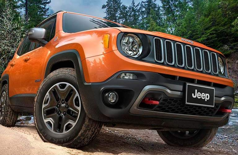 orange 2016 Jeep Renegade driving through mud and water