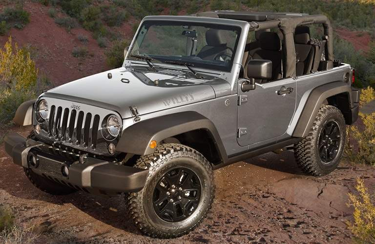 silver 2016 Jeep Wrangler parked on dirt hill